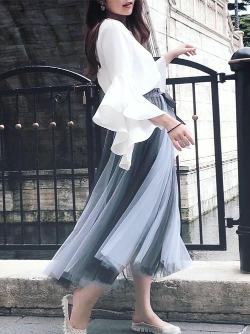 フレアスリーブブラウスにグレーフィッシュテールチュールスカートを履いた女性