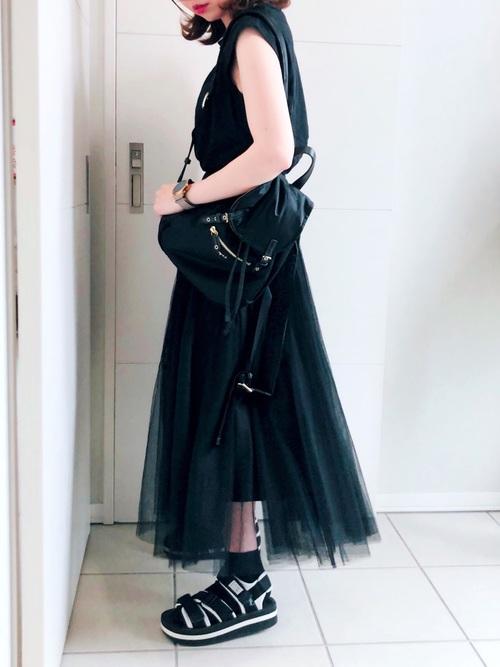黒コットンクルーネックノースリーブに黒チュールロングスカートを履いた女性