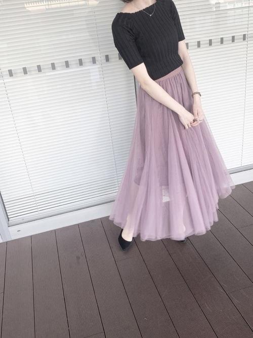 ハーフスリーブニットにピンクロングチュールスカートを履いた女性