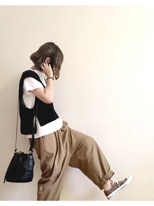 サイドスリットベストとサルエルパンツを着た女性