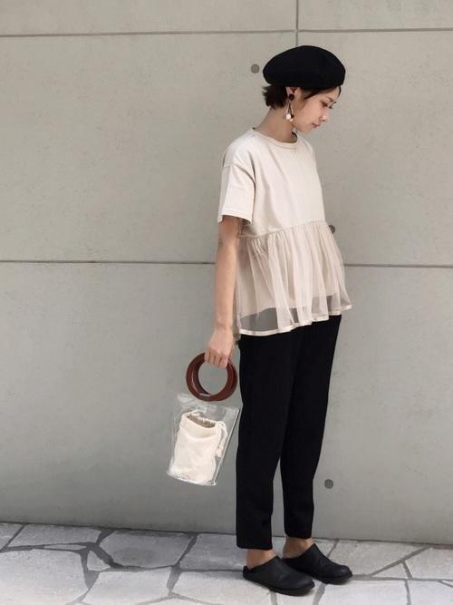 ペプラムTシャツを着てハンチングをかぶった女性