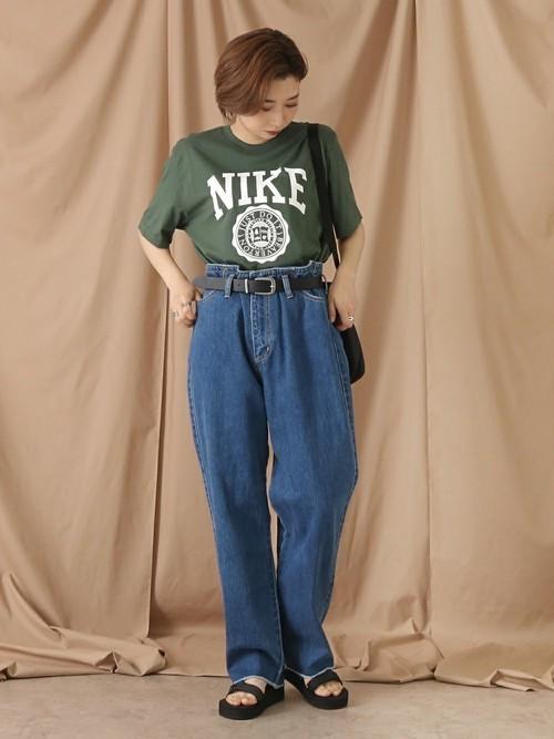 NIKEのグリーンTシャツとハイウエストデニムパンツを着た女性