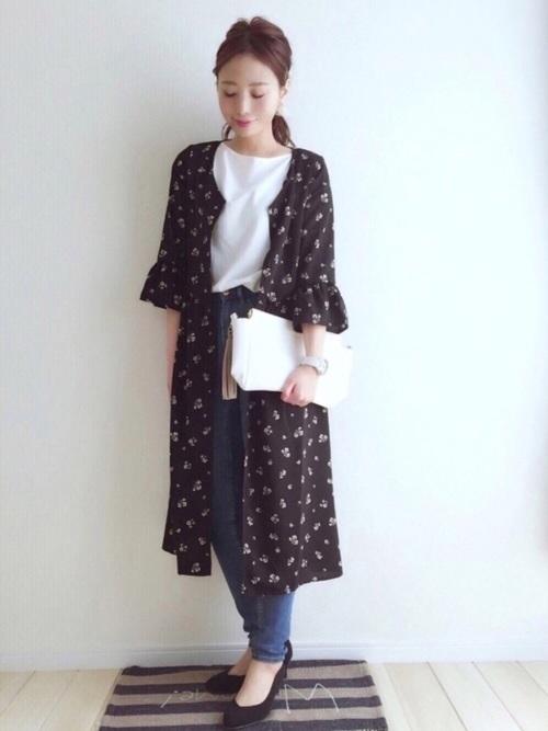 黒ロング花柄カーディガンにスキニーデニムパンツを履いた女性