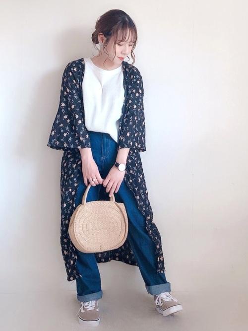 黒ロング花柄カーディガンにスリムデニムパンツを履いた女性