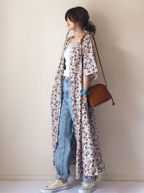 白ロング花柄カーディガンにデニムジーンズを履いた女性