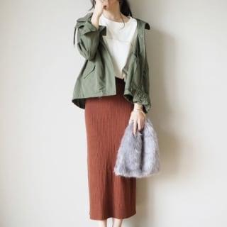 カーキマウンテンパーカーにミディ丈リブスカートを履いた女性