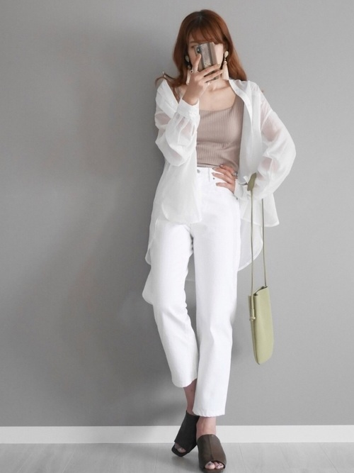 ベージュのタンクトップに白のシアーシャツと白のパンツのコーデ