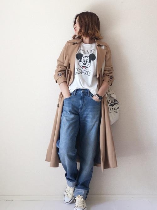 トレンチコートとTシャツにデニムパンツを履いた女性