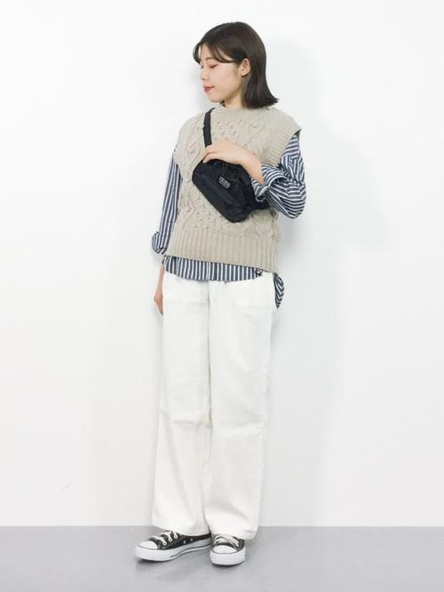 ストライプスキッパーシャツとケーブルニットベストに白コーデュロイワイドパンツを履いた女性