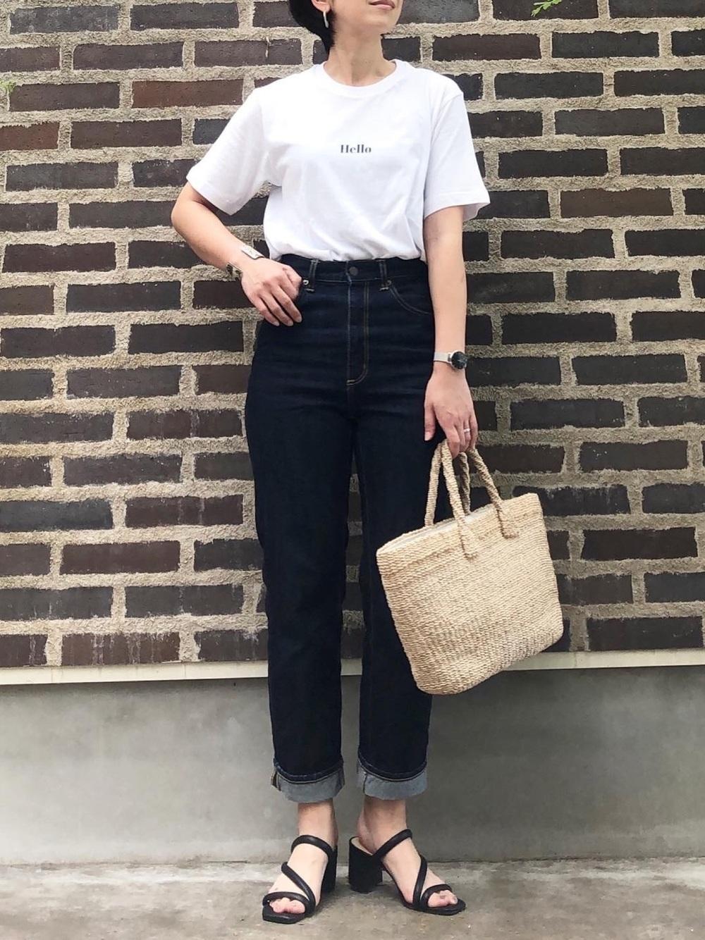 しまむらのブラウンのかごバッグを持って白Tシャツとインディゴデニムを着た女性