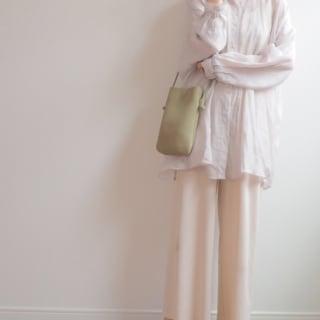 ベージュのシャツとパンツにGUで値下げしているグリーンのマシュマロフラットパンプスを履いた女性