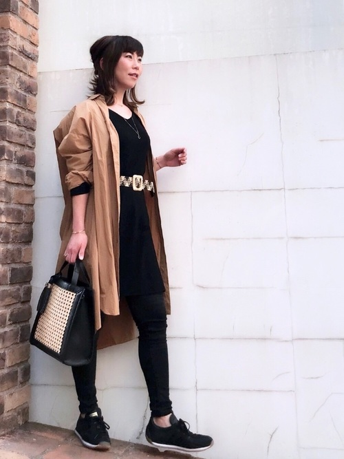 ベージュシャツワンピースと黒スキニーパンツに黒スニーカーを履いた女性