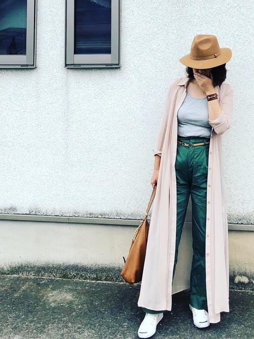 ベージュシャツワンピースとグレータンクトップにグリーンチノパンツを履いた女性