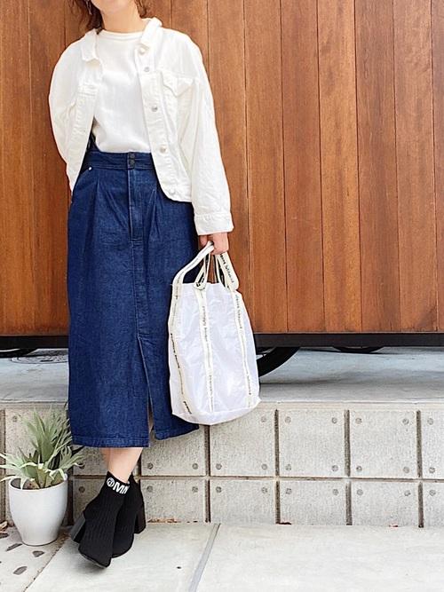 ホワイトデニムジャケットとデニムスリットスカートに黒ブーティを履いた女性