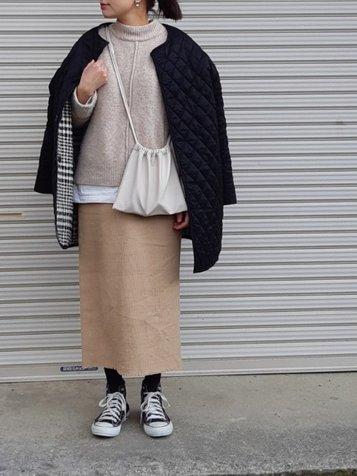 黒キルティングコートとハイネックニットトップスにベージュタイトスカートを履いた女性