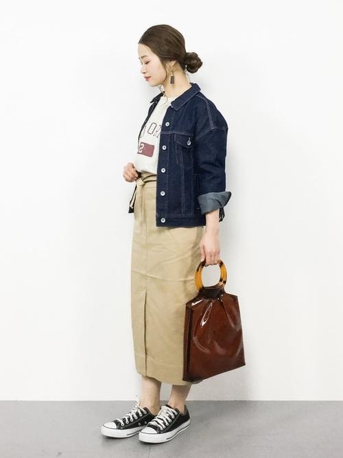 デニムジャケットとスウェットプルオーバーにベージュタイトスカートを履いた女性
