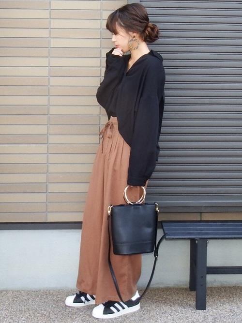 黒スキッパーシャツとブラウンワイドパンツに黒アディダススーパースターを履いた女性