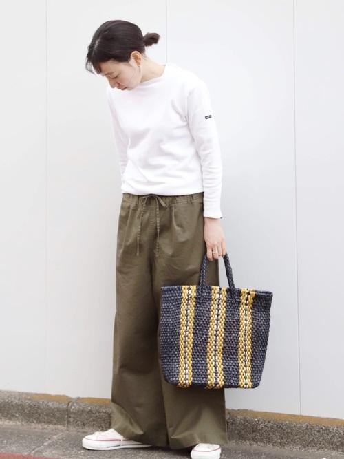 グリーンストライプカゴバッグと白ポートネックプルオーバーにカーキドロストワイドパンツを履いた女性