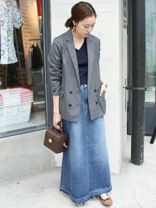 ダブルテーラードジャケットとワイドリブ Vネックプルオーバーにフレアーロングデニムスカートを履いた女性