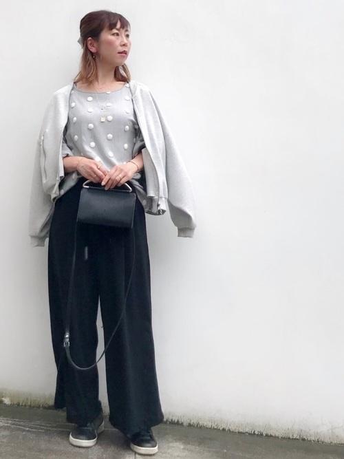グレープラッシュボンバージャケットとドット柄ブラウスに黒ワイドパンツを履いた女性