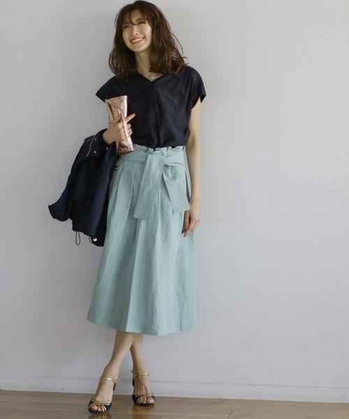 ネイビーのフレンチスリーブのシャツにパステルブルーのフレアスカートを合わせた女性