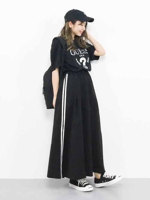 GUESSのラメプリント黒Tシャツとサイドラインスカートに黒ローカットスニーカーを履いた女性