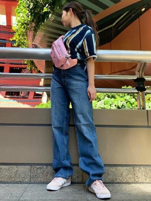 太ストライプTシャツとハイライズストレートデニムパンツにGUESSのピンクウエストポーチを身に着けた女性