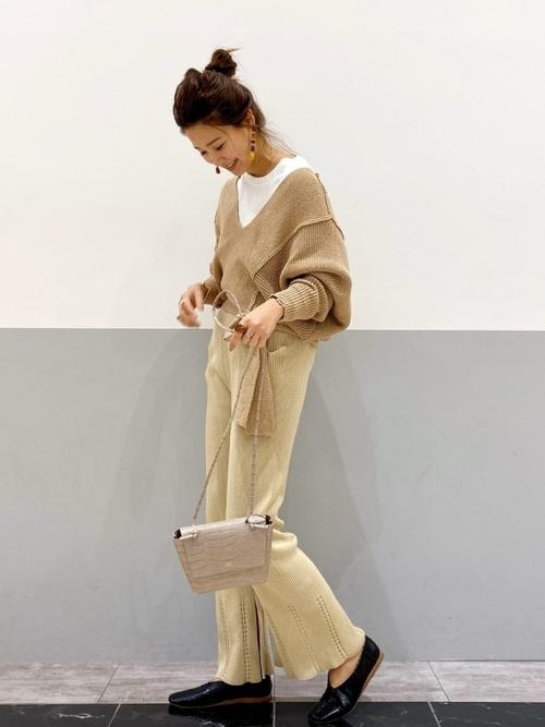 ブラウンブークレVネックニットにベージュ裾透かし編みニットパンツを履いた女性