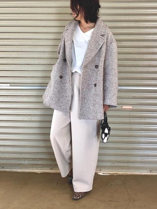 グレーヘリンボーンオーバージャケットコートにベージュコクーンパンツを履いた女性