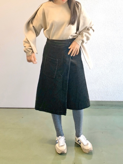 コーデュロイラップスカートとドッキングニットにスポーティースニーカーを履いた女性