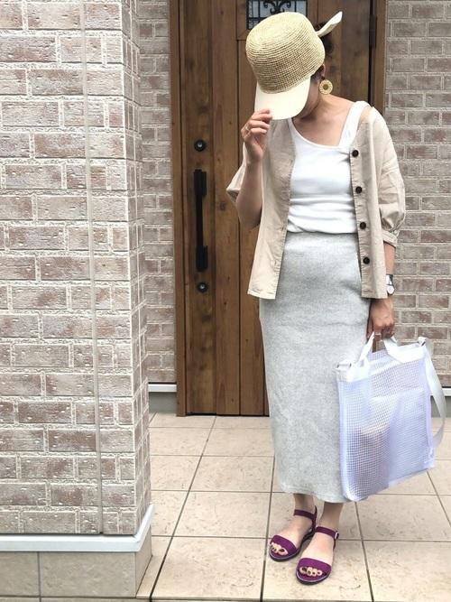 タイトロングスカートとフロントボタンブラウスにフラットサンダルを履いた女性