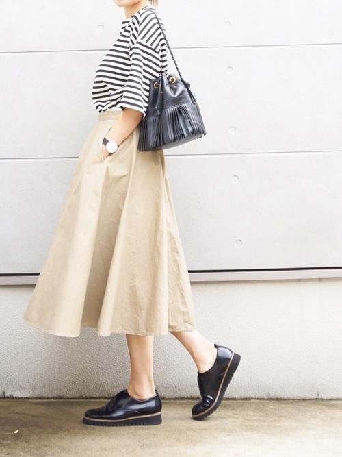 コットンスカートとボーダーTシャツにドレスシューズを履いた女性