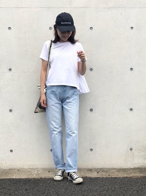 白シャツにデニムパンツを履いた女性