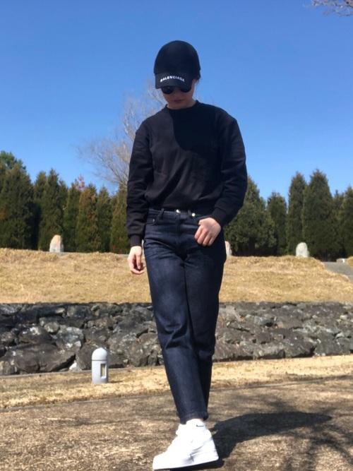 デニムパンツに黒のカットソーを着た女性