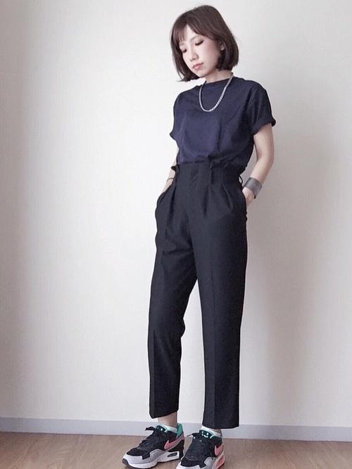ユニクロのクルーネックネイビーTシャツと黒アンクルパンツにスポーティースニーカーを履いた女性