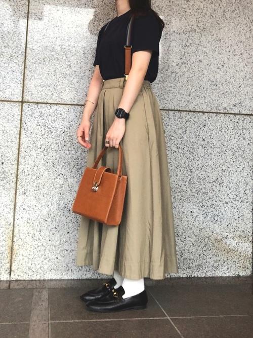 ユニクロのネイビーTシャツとベージュチノロングスカートにビットローファーを履いた女性