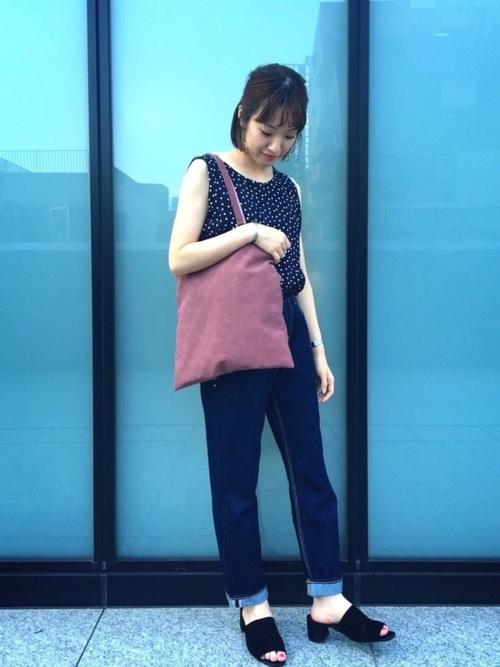 ドット柄ノースリーブシャツとハートマーケットのデニムパンツに黒ミュールサンダルを履いた女性