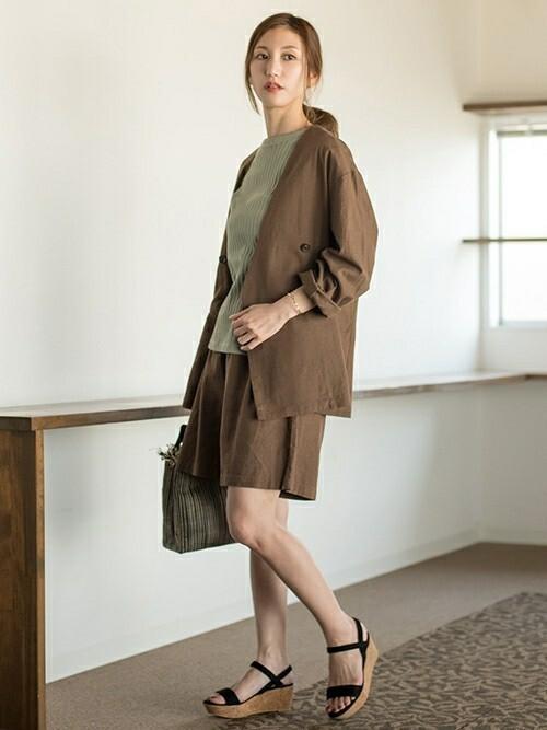 ブラウンノーカラージャケットとセットアップハーフパンツに黒ウェッジソールサンダルを履いた女性