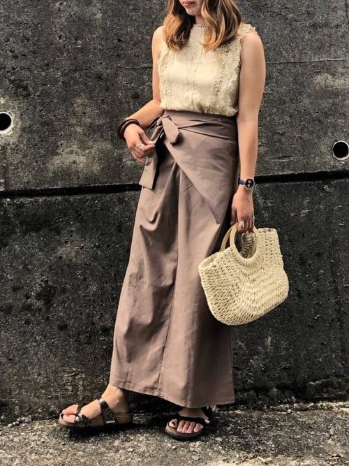 ベージュ層レースノースリーブタンクトップにブラウンリネンラップロングスカートを履いた女性