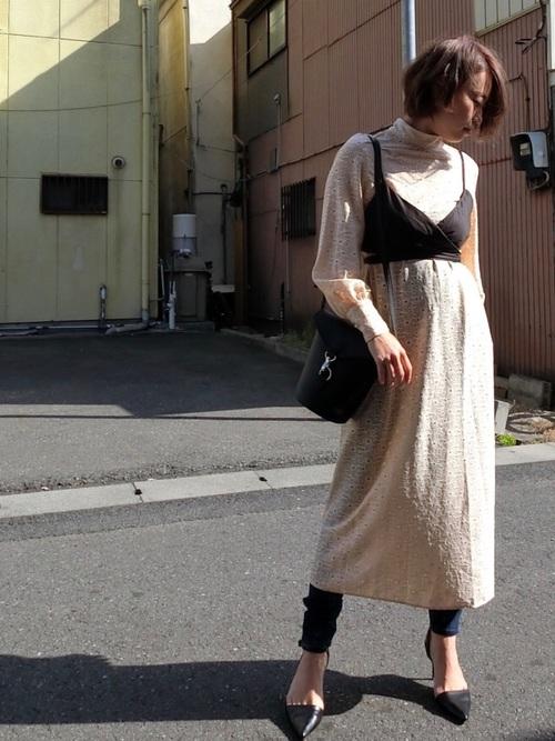 ベージュレースドレスワンピースに黒ビスチェを着た女性