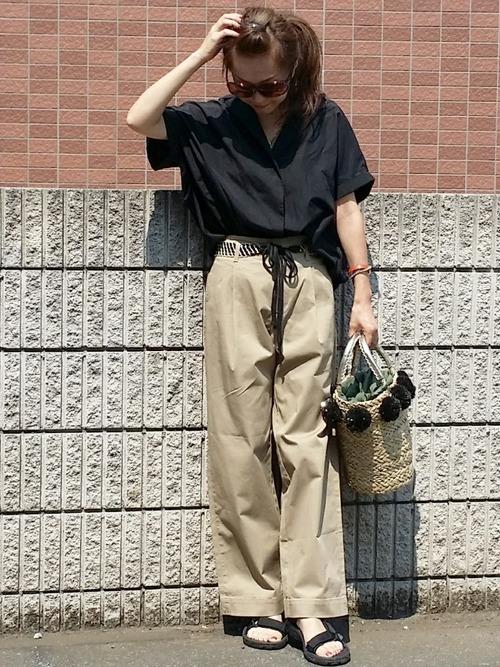 黒オープンカラーコクーンシャツにベージュハイウェストチノパンツを履いた女性
