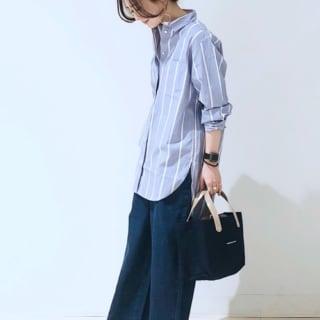 サックスブルーストライプシャツチュニックにグレーワイドデニムパンツを履いた女性
