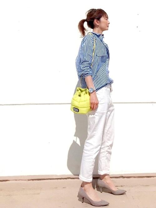 ブルーストライプシャツワンピースにホワイトデニムテーパードパンツを履いた女性