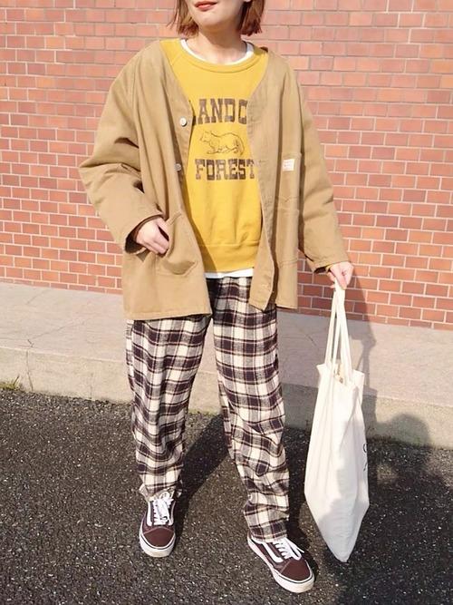 イエローロゴスウェットにベージュビッグシルエットノーカラーカバーオールを着た女性