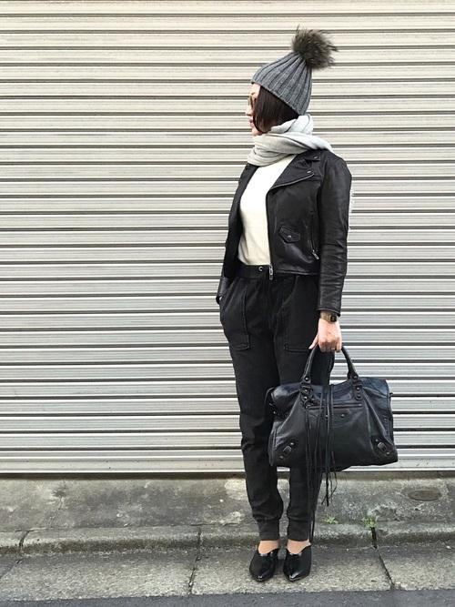 黒ライダースジャケットに黒スウェットパンツを履いた女性