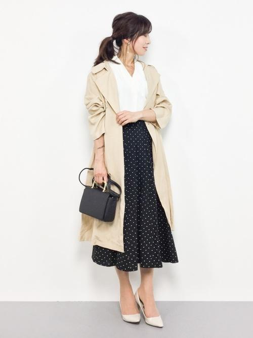 トレンチコートと黒ドット柄フレアスカートにパンプスを履いた女性
