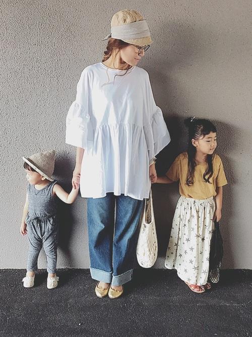 ビッグブラウスとワイドデニムパンツゴールドパンプスを履いた女性