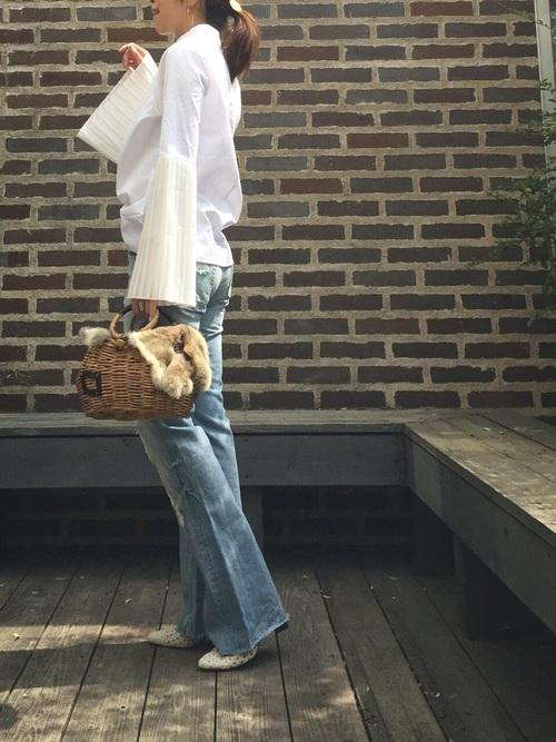 袖フリルブラウスとワイドデニムパンツにかごバッグをもった女性