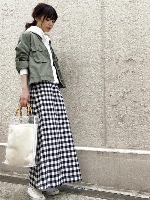 ミリタリージャケットと【GU】スウェットパーカーにチェックAラインロングスカートを履いた女性