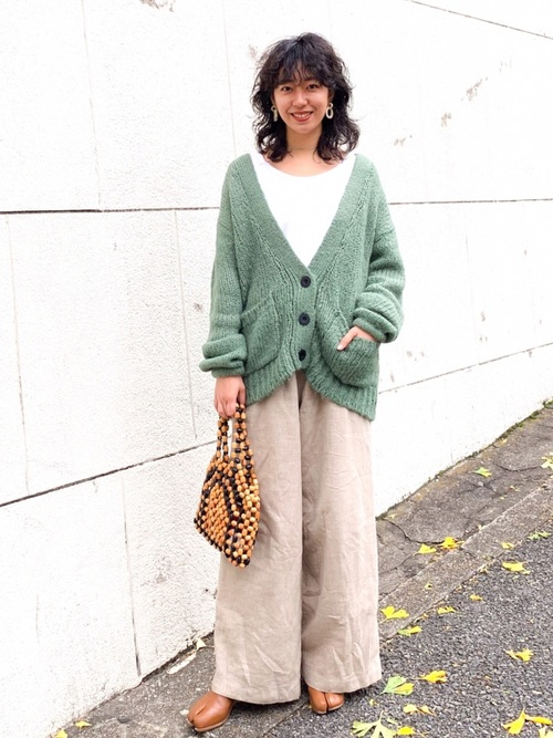 Vネックローゲージニットカーディガンと白インナーカットソーにソフトウールパンツを履いた女性